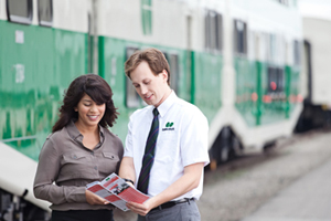 Commuter and Metrolinx employee in front of GO Train